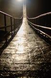 Zawieszenie most w ciemnej jamie obraz stock