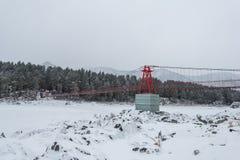 Zawieszenie wiszący most nad zima marznąca rzeka zdjęcia royalty free