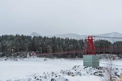 Zawieszenie wiszący most nad zima marznąca rzeka zdjęcia stock