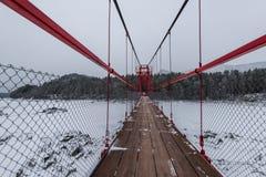 Zawieszenie wiszący most nad zima marznąca rzeka obraz royalty free