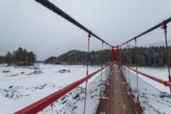 Zawieszenie wiszący most nad zima marznąca rzeka obraz stock