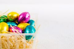 Zawijający czekoladowi cukierki z jajko formą w plastikowym koszu zdjęcie royalty free