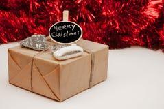 Zawijający Christmass prezenta pudełko na czerwonym iskrzastym backgrou obraz stock