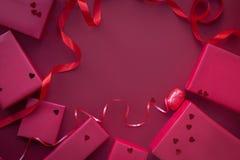 Zawijający czerwoni prezentów pudełka na czerwonym tle z confetti kosmos kopii obrazy royalty free