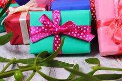 Zawijający kolorowi prezenty dla bożych narodzeń i jemioły na starym drewnianym tle Obraz Stock