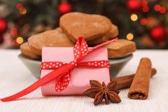 Zawijający prezent, miodowniki i choinka z światłami w tle, zdjęcie royalty free