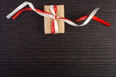Zawijający prezent z faborkiem dla walentynka dnia, miejsce dla teksta na czerni desce zdjęcie royalty free
