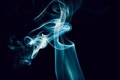 Zawijasy błękit dymią na czarnym tle Fotografia Royalty Free