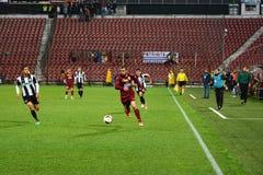 Zawodnik środka pola dribling podczas futbolowego dopasowania Zdjęcie Stock
