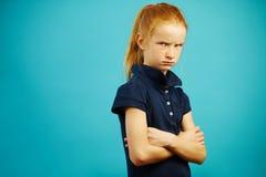 Zawodząca dziewczyna z gniewnymi wyrażenie stojakami na odosobnionym błękitnym tle, wyraża frustrację lub niezadowolenie fotografia stock