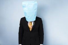 Zawstydzony biznesmen z torbą nad jego głową Fotografia Stock