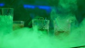Zazębeni napoje w szkłach z słoma na barze odpierającym w dymu na tle barwione lampy zbiory