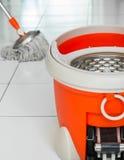 Zazzera e secchio rotatori sulla pavimentazione in piastrelle Fotografia Stock