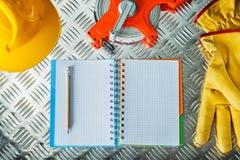 Zbawcza rękawiczka ciężkiego kapeluszu taśmy notatnika ołówka miara dalej gofruje fotografia stock