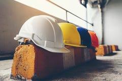 Zbawczy hełm, biel, kolor żółty, błękit i pomarańcze umieszczający na cementowej podłodze w budowie, fotografia royalty free