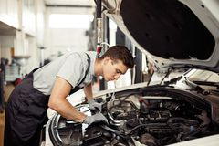 Zbawczy sirst: atrakcyjny samochodowy mechanik sprawdza silnika obraz royalty free