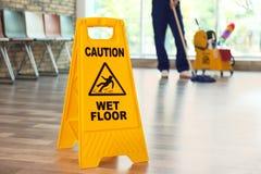 Zbawczy znak z zwrot ostrożności mokrą podłoga fotografia stock
