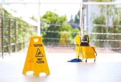 Zbawczy znak z zwrot ostrożności mokrą podłoga zdjęcie royalty free