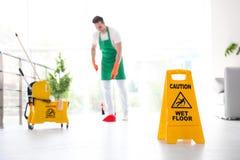 Zbawczy znak z zwrot ostrożności MOKRĄ podłoga i młodym pracownikiem na tle zdjęcie royalty free