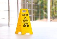 Zbawczy znak z zwrot ostrożności mokrą podłoga, indoors obrazy stock