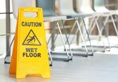 Zbawczy znak z zwrot ostrożności mokrą podłoga, indoors obraz stock