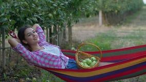 Zbiera sezon i cieszy się relaksować, uśmiechnięta kobieta z koszem owoc kłamstwa w hamaku zbiory