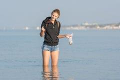 Zbiera skorupy przy morzem w ranku wcześnie Zdjęcia Royalty Free