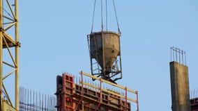 Zbiornik z betonem dostarczał żurawiem na placu budowym, robot budowlany obrazy stock