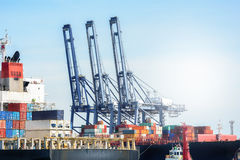 Zbiornika ładunku zafrachtowań statek z pracującym żurawia mostem w stoczni przy mrocznym niebem Obraz Stock