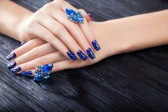 Zbita szyba błękitny manicure na czarnym tle fotografia stock