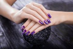 Zbitych szyb purpur manicure na czarnym tle zdjęcia stock