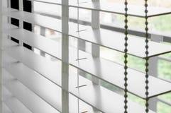 Zbliżenie białego koloru drewniana stora z białymi drabinowymi taśm zasłonami Światło słoneczne przez okno w mieście z ogródem Se obrazy stock
