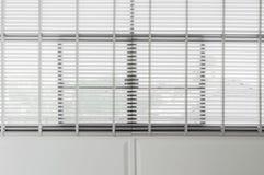 Zbliżenie białego koloru drewniana stora z białymi drabinowymi taśm zasłonami Światło słoneczne przez okno w mieście z ogródem Se obrazy royalty free
