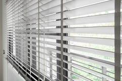 Zbliżenie białego koloru drewniana stora z białymi drabinowymi taśm zasłonami Światło słoneczne przez okno w mieście z ogródem Se obraz stock