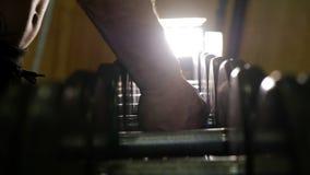 Zbliżenie bierze dumbbells męska ręka, siły stażowy wyposażenie w gym zbiory wideo
