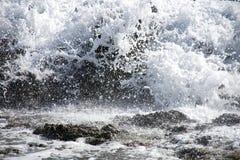 Zbliżenie fale nad zanurzającym skały tłem obraz stock