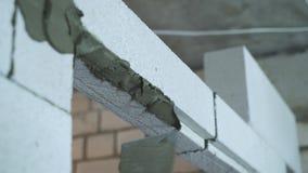 Zbliżenie kładzenie moździerz na wietrzącym betonowym bloku z szpachelką zbiory