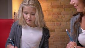 Zbliżenie krótkopęd kamery chodzeniem od ręk rysuje mała ładna dziewczyna robi obrazkowi z ołówkiem i jej mamą zbiory