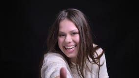 Zbliżenie krótkopęd młoda atrakcyjna caucasian brunetki kobieta pokazuje kciuk w górę i śmia się szczęśliwie przed zdjęcie wideo