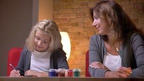 Zbliżenie krótkopęd młoda kobieta i jej mała ładna córka rysunkowa wpólnie i egzamininujący farby zbiory