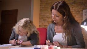Zbliżenie krótkopęd macierzysty młody caucasian homeschooling jej małej ładnej córki przy wygodnym domem indoors zbiory