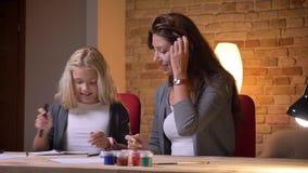 Zbliżenie krótkopęd patrzeje kamerę mała ładna dziewczyna i jej młoda caucasian matka przygotowywa jej childfor szkoły i zbiory wideo