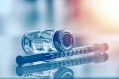 Zbliżenie medycyny grypa, buteleczka, odry krowiankowa butelka z strzykawką i igła dla immunizacji na rocznika medycznym tle lub, obraz stock