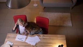 Zbliżenie odgórny widok potomstwa macierzyści pomagać jej małej córki z sztuki pracą domową przy wygodnym domem indoors zbiory wideo