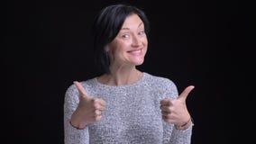 Zbliżenie portret dorosła caucasian rozochocona kobieta radośnie pokazuje kciuki ono uśmiecha się i podczas gdy patrzejący prosto zbiory