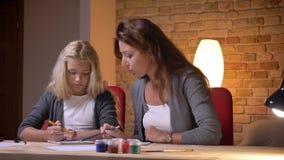 Zbliżenie portret młoda caucasian matka ocenia jej małych ładnych córek matematycznie umiejętności przy wygodnym domem indoors zbiory wideo