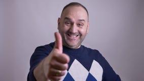 Zbliżenie portret w średnim wieku caucasian samiec pokazuje kciuk w górę i ono uśmiecha się podczas gdy patrzejący kamerę zdjęcie wideo