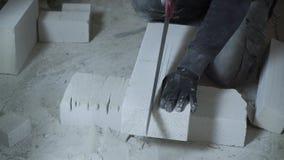 Zbliżenie pracownika budowlanego piłowanie wietrzył betonowego blok według ocen zbiory