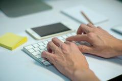Zbliżenie selekcyjna ostrość na rękach pisać na maszynie na klawiaturze z defocused stationaries i telefonie komórkowym w tle biz obraz royalty free