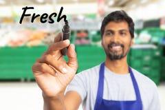 Zbliżenie sklepu spożywczego pracownika pisać świeży na pokazie zdjęcia stock